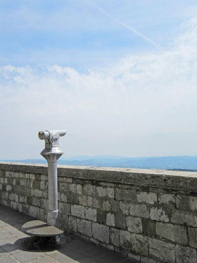 Binoculars By Retaining Wall Against Sky`