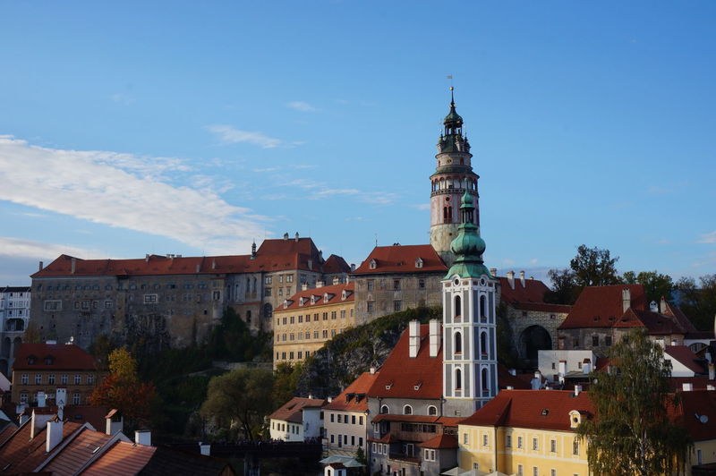 Low angle view of cesky krumlov castle and st jost church against sky