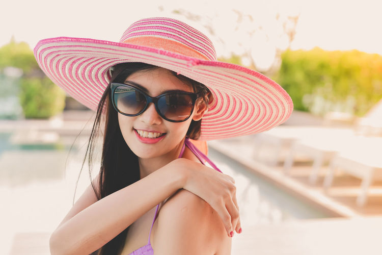 Smiling Young Woman Wearing Sunglasses And Hat At Poolside