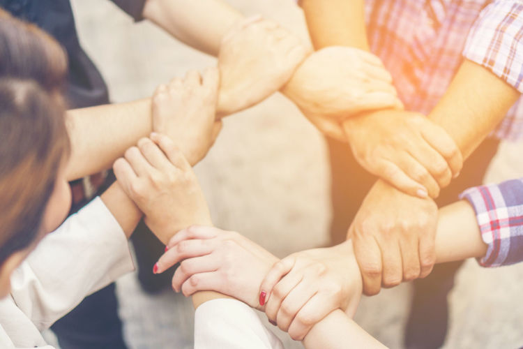 Close-up of friends holding hands while huddling outdoors
