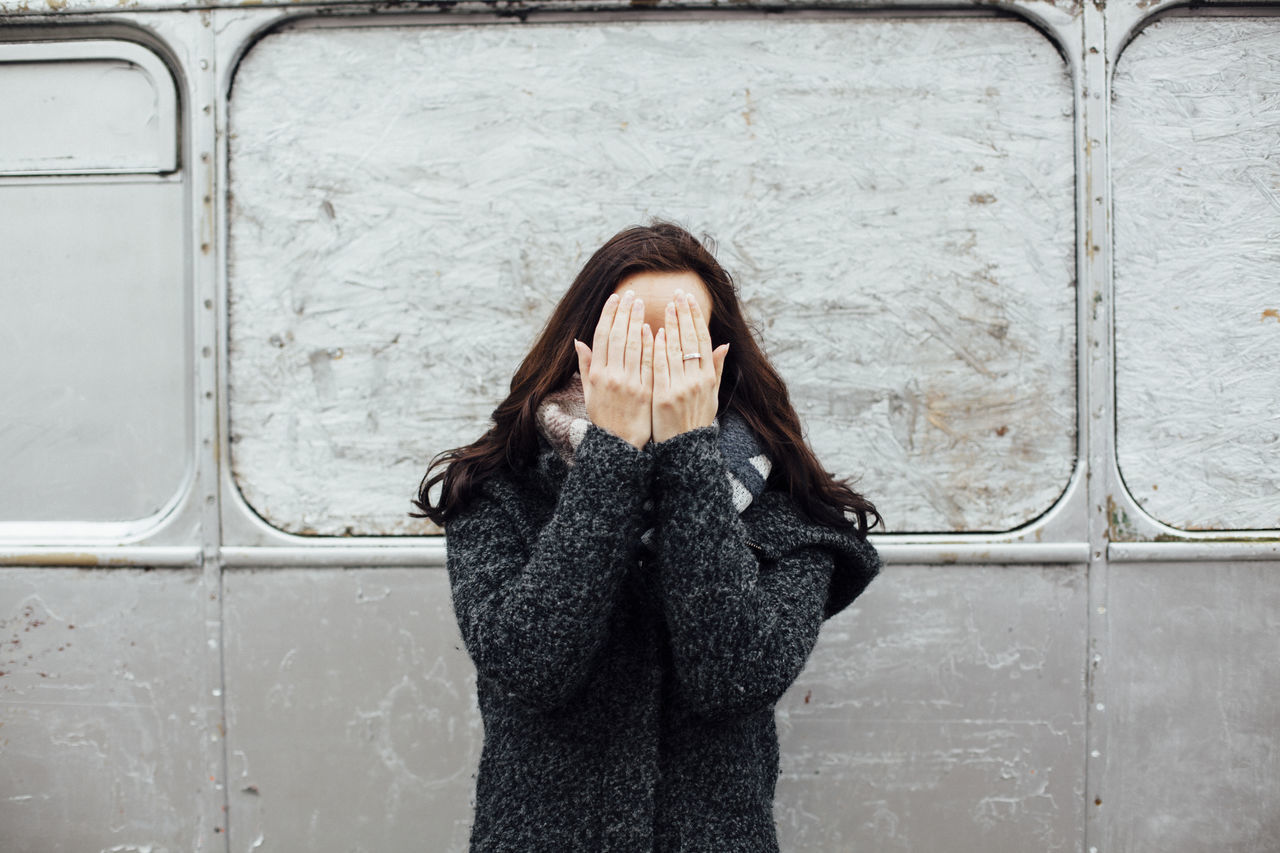 Young Woman Covering Face Against Vehicle