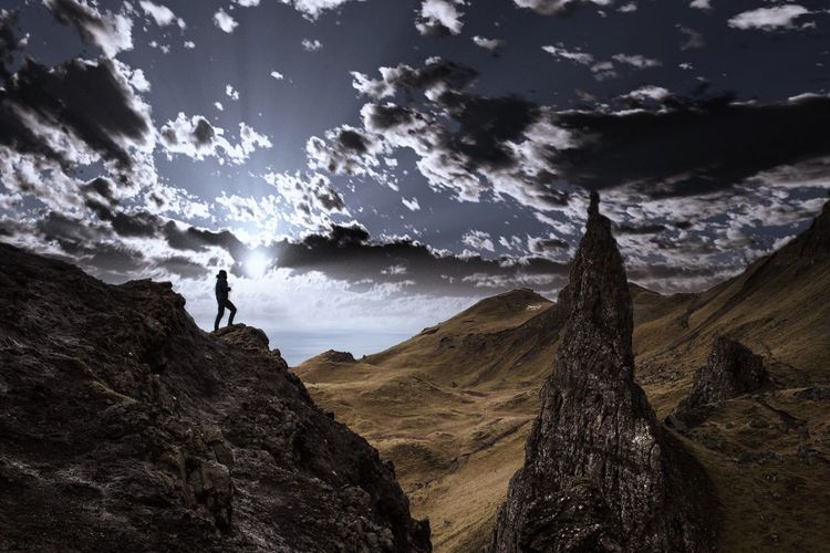 Low angle view of silhouette person standing on rocky mountains against cloudy sky