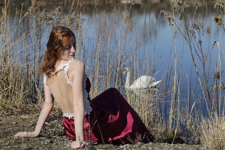 Young woman sitting at lakeshore