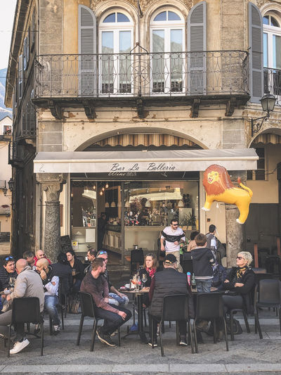 People sitting at restaurant by buildings in city