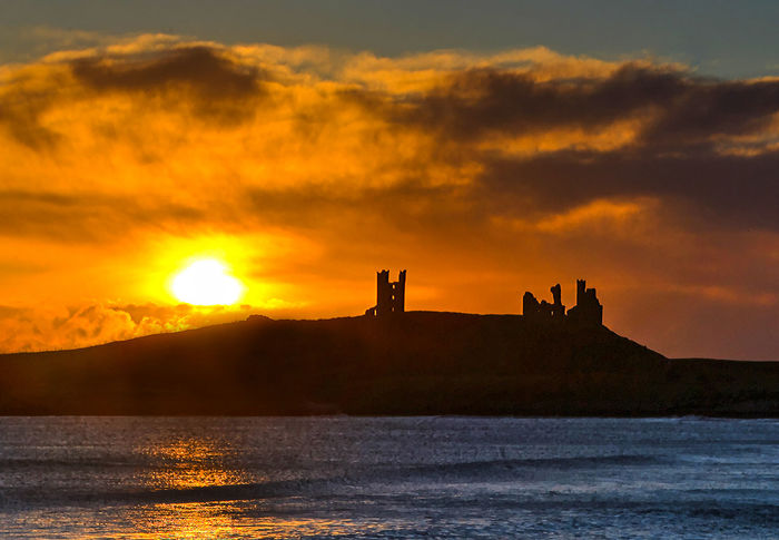 Cliffside castle Dunstanburgh Castle Beauty In Nature Castle On A Hill Cliffside Nature No People Orange Color Outdoors Promantory Scenics Silhouette Sky Sunlight Sunset Tranquility Water Waterfront