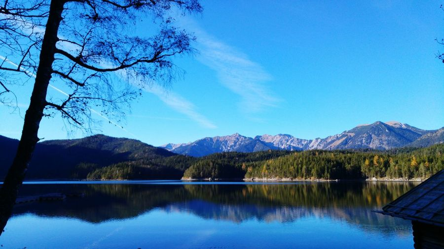 Mountains and trees reflecting in lake against sky