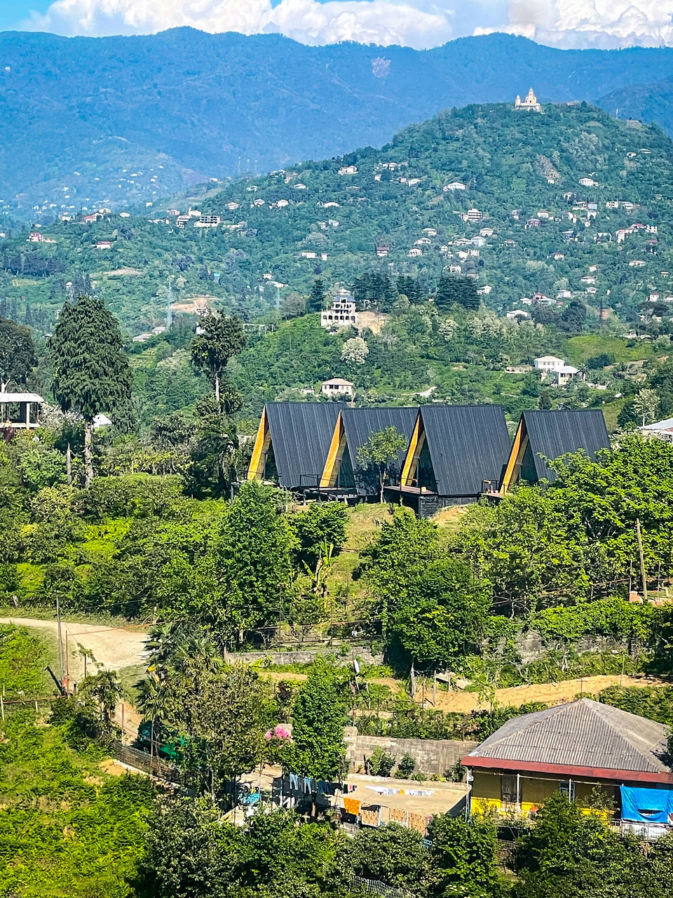 HIGH ANGLE VIEW OF TREES AND BUILDINGS AGAINST MOUNTAIN