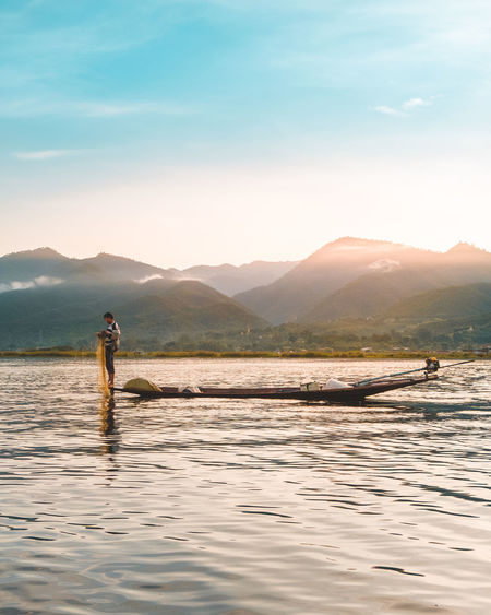 ASIA Beauty In Nature Fish Fisherman Inle Lake Leisure Activity Lifestyles Men Mountain Mountain Range Myanmar Nature Nautical Vessel Non-urban Scene One Person Outdoors Real People Scenics - Nature Sky Standing Sunlight Tranquil Scene Tranquility Water Waterfront
