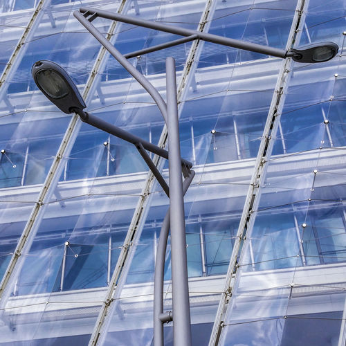 Low angle view of street lights against modern building