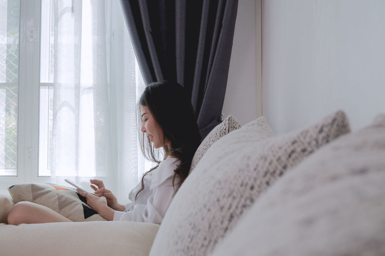 young asian woman using mobile in living room. Bed Happy Mobile Phone Morning Room Vacations Asian Girl Connection Curtain Emotion Enjoying Life Find Furniture Happy Time Indoors  Lifestyles Living Room Mobile Relaxing Moments Searching Sofa Summer Touching Using Phone Window