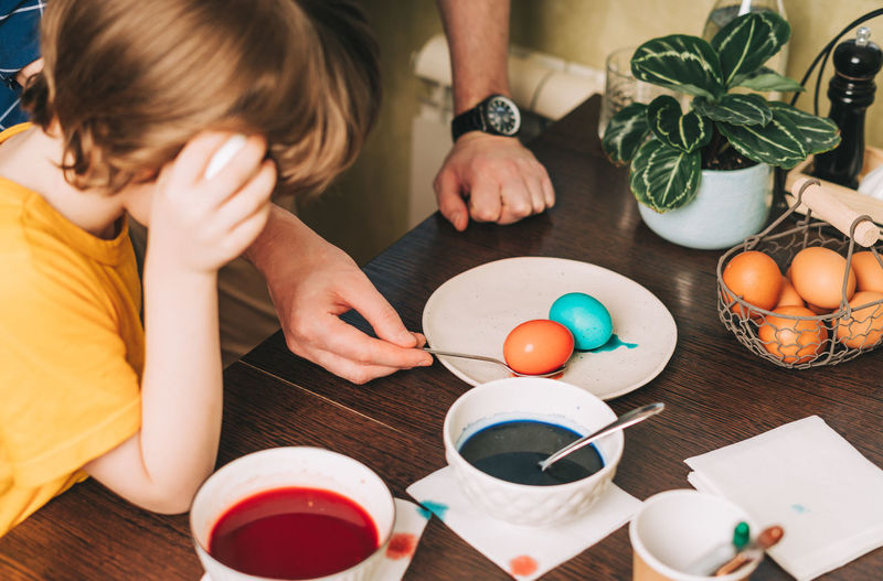 Easter day. father and son painting eggs. family  in a kitchen. preparing, creative homemade decor