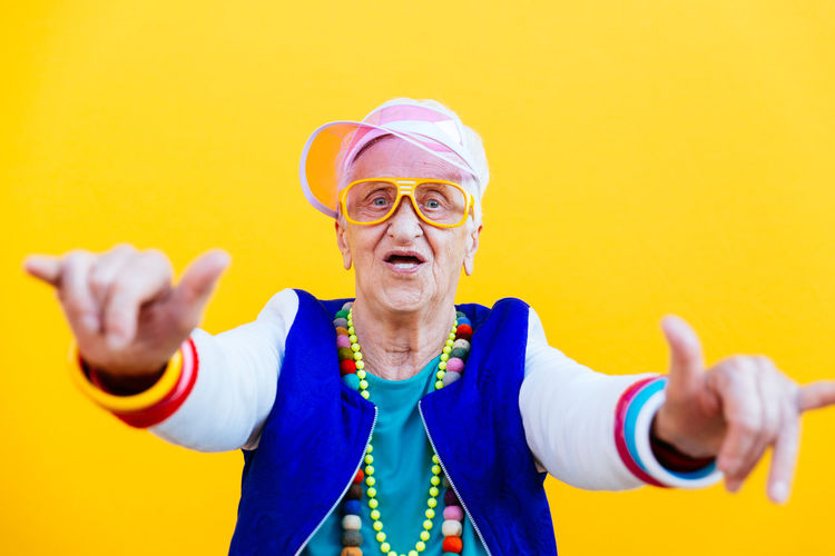 Portrait of smiling senior woman dancing against yellow background