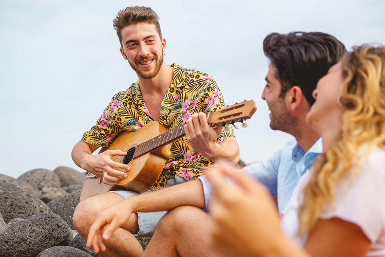 Group of people playing guitar and singing in the seaside on summer