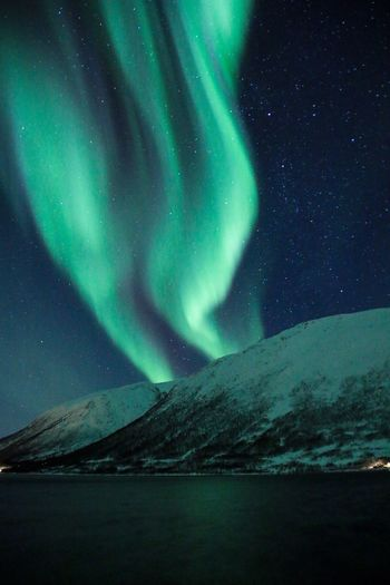 Scenic View Of Sea By Snowcapped Mountains Against Aurora Polaris