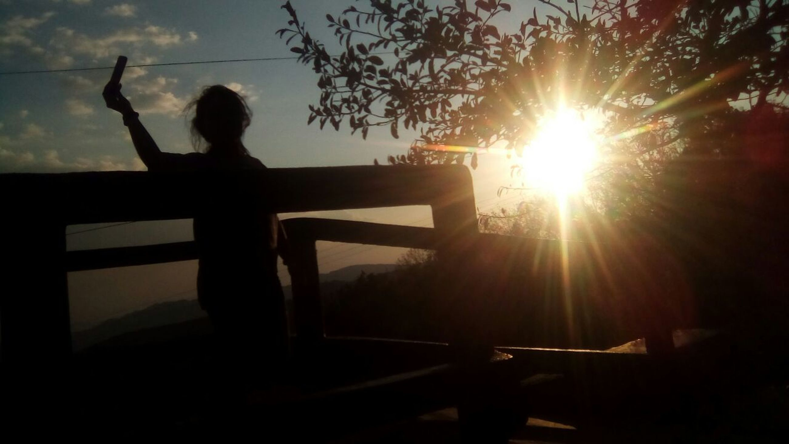 silhouette, sunlight, sun, lens flare, railing, sunset, sunbeam, one person, leisure activity, lifestyles, women, outdoors, real people, tree, nature, beauty in nature, sky, men, day, adult, people