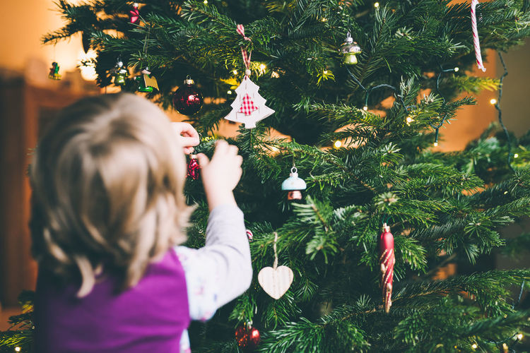 little girl decorates the christmas tree Celebration Child Childhood Christmas Christmas Decoration Christmas Ornament Christmas Tree Close-up Day Decoration Girls Indoors  One Girl Only One Person Real People Tradition Tree