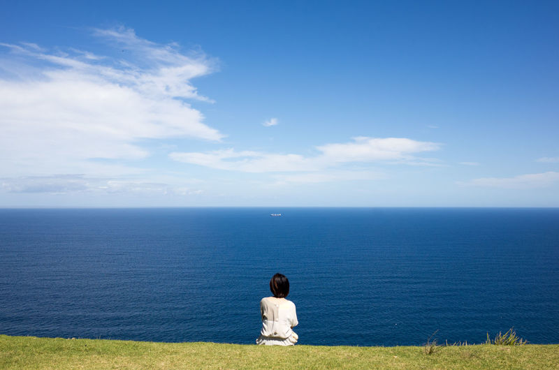 Rear view of woman looking at seascape against sky