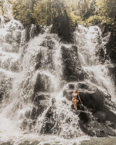 Travel Destinations Beauty In Nature Tropical Tropical Paradise Jungle Having Fun Bali Indonesia Kanto Lampo Rock Formation Rock - Object Closer To Nature Enjoying Nature Water Flow Bathing In A Waterfall Sitting On A Rock Waterfall One Young Woman Only Water Nature Motion Day Tree Lifestyles People Splashing Outdoors Real People Plant Leisure Activity Wet