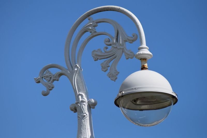 Low angle view of street light against clear blue sky