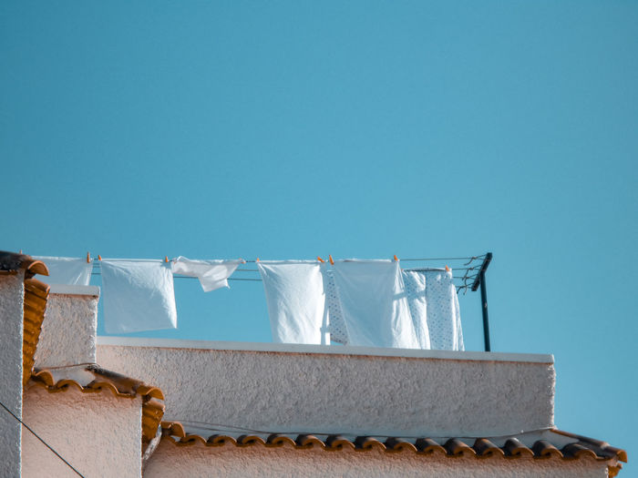 Low angle view of clothes drying against blue sky