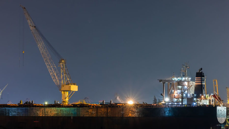 Illuminated cranes at commercial dock against sky at night