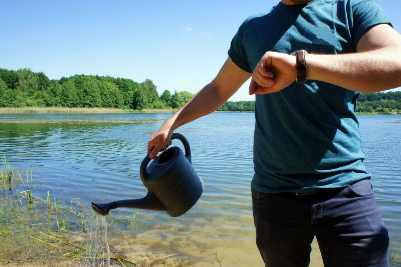 Midsection Of Man Checking Time While Holding Watering Can In Lake