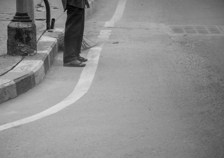 Low Section Of Man Standing On Road