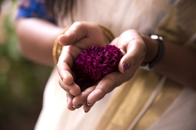 Close-up of woman in sari holding flower