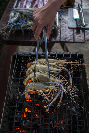 Cropped Hand Grilling Crayfish On Barbecue
