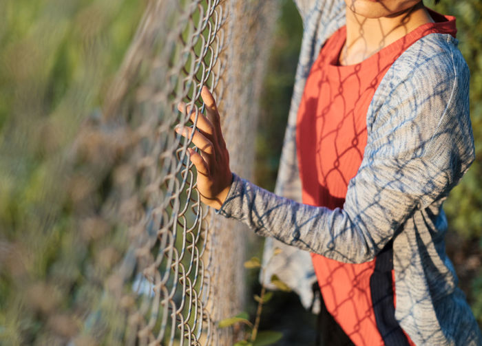Midsection of woman standing by fence on field