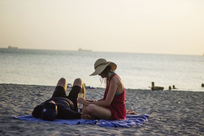EyeEm Selects Sea Beach Adult Togetherness Horizon Over Water Adults Only Two People Sitting People Vacations Outdoors Sunset Day Women Men Water Only Women Sky Full Length Young Women