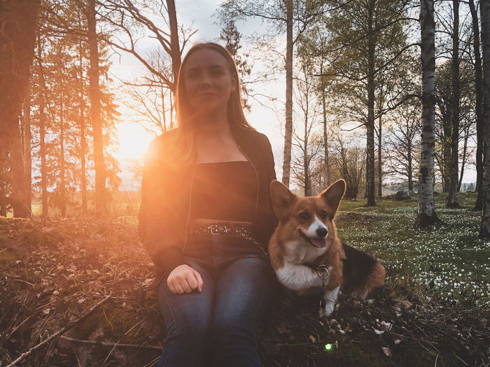 Woman sitting with dog in forest