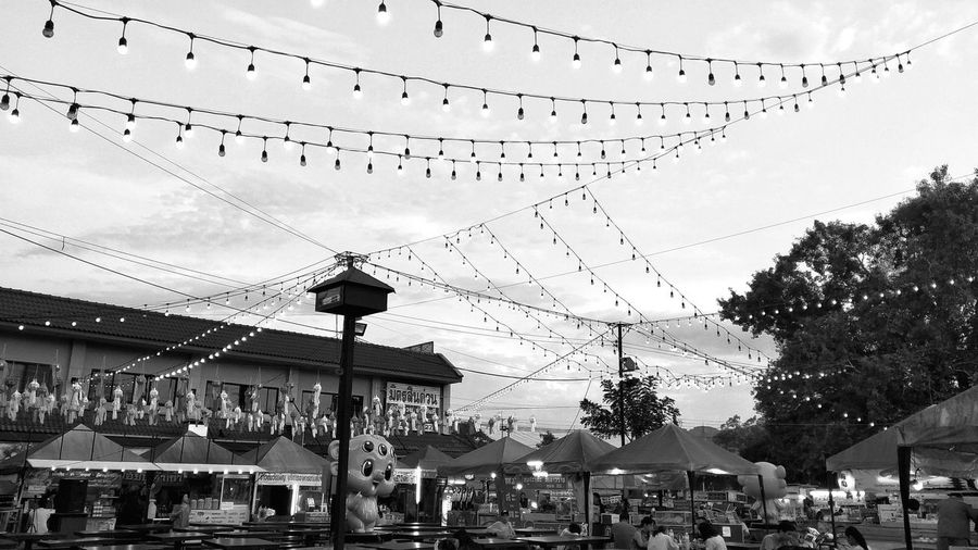 People in amusement park by buildings against sky