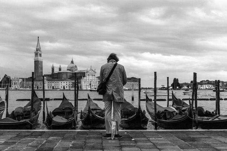 Rear view of man standing by gondolas
