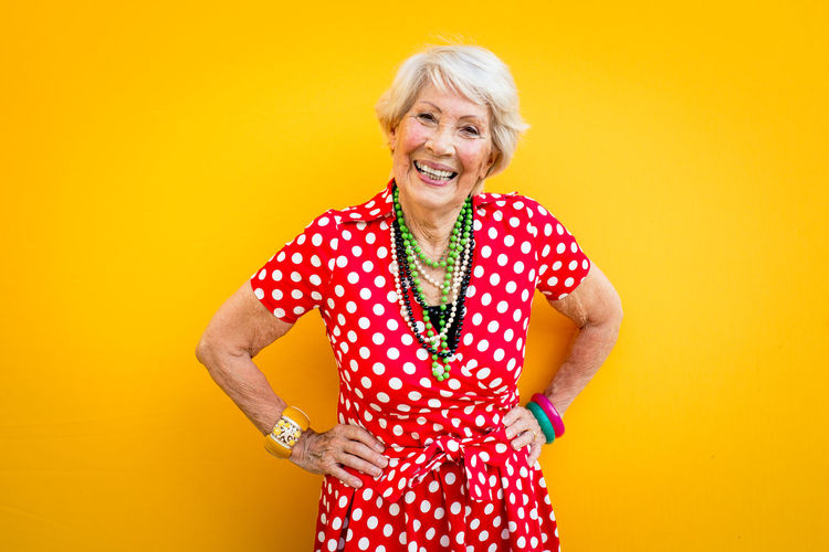 Portrait of smiling senior woman standing against yellow background