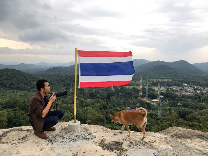 Man Photographing Flag With Dog Against Landscape