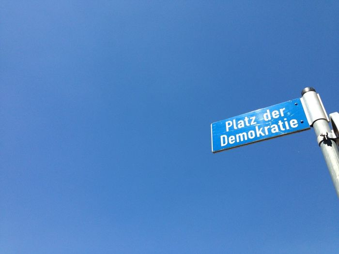 Democracy Square Blue Clear Sky Communication Low Angle View Road Sign Text