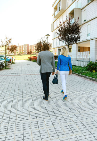 Unrecognizable businessman and businesswoman walking towards their office Business Couple Man Sunlight Woman Worker Working Business Finance And Industry Businessman Businesswoman Caucasian Colleague Document Dossier Executive  Flare Lifestyles Office Building Outdoors Real People Street Sun Two People Vertical Young Adult
