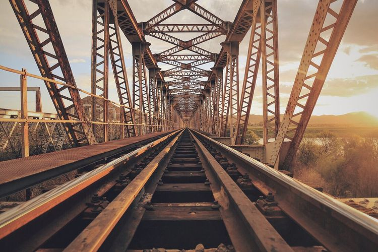 Empty railway bridge against sky during sunset