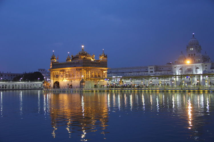 Illuminated golden temple by lake against sky at dusk