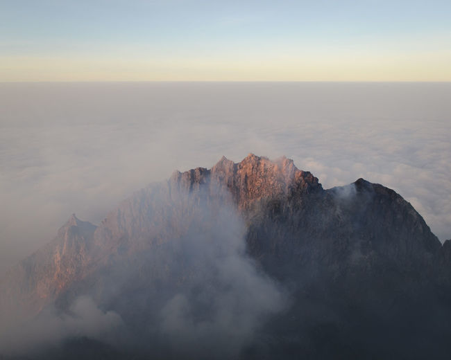 Scenic view of mountain covered in fog against sky