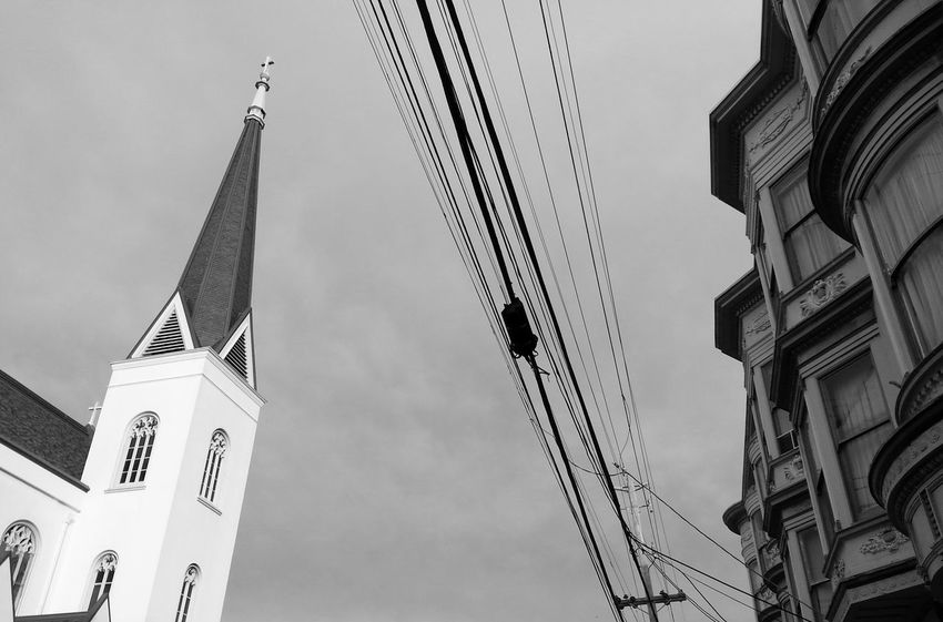 Separation of church and estates... Architecture Black And White Church Division Low Angle View Monochrome Outdoors Power Lines Religion San Francisco Sky Snapseed Steeple Utility Pole Wires