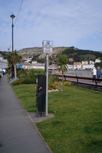 Welsh and English language sign for pay and display parking. Llandudno, North Wales, on the Creuddyn peninsula. Bench Creuddyn Peninsula Grass Parking Meter Architecture Beauty In Nature Built Structure Cloud - Sky Communication Day Grass Great Orme Guidance Llandudno Nature North Wales Outdoors Scenics Sky Street Lighting Tree Water