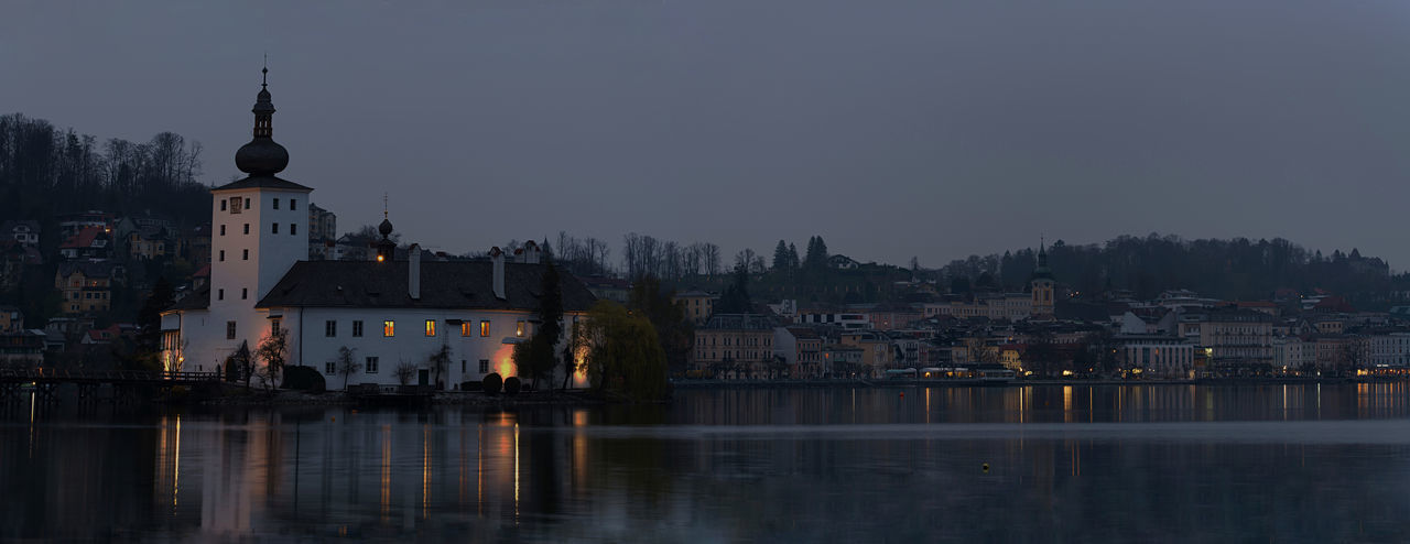 Buildings by river against sky in city at dusk