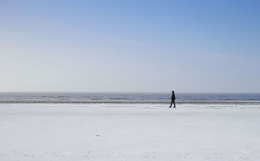 Side View Of Man Walking At Snowcapped Beach During Winter