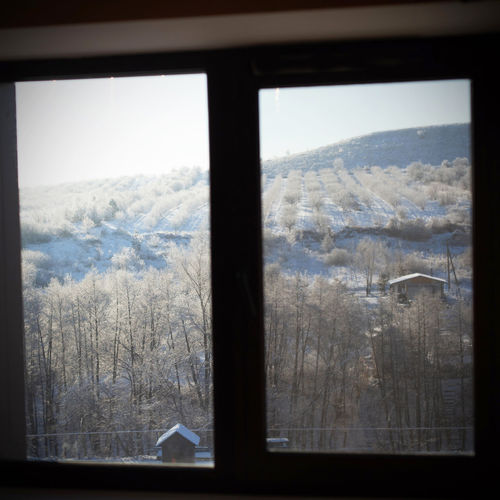 Scenic view of snow covered landscape seen through glass window