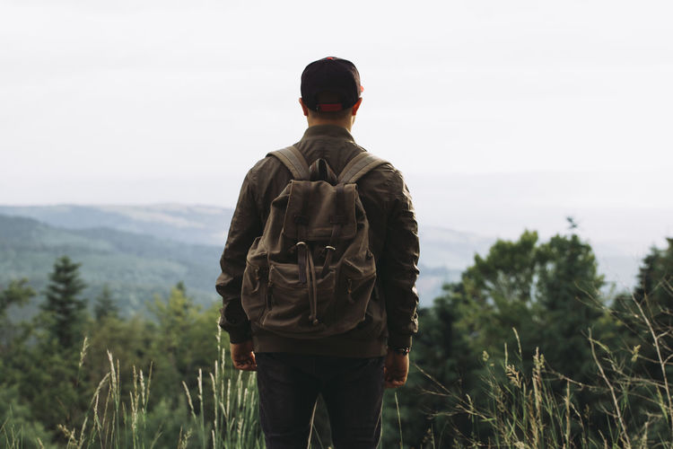 Adventure Backpack Beauty In Nature Casual Clothing Day Focus On Foreground Grass Hiking Landscape Leisure Activity Lifestyles Men Mountain Nature One Person Outdoors People Real People Rear View Scenics Sky Sky And Clouds Standing Tranquility Walking