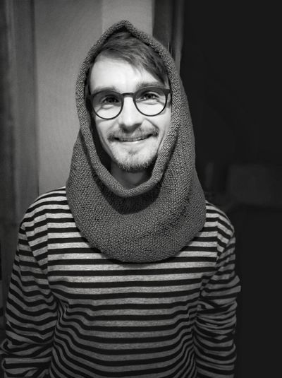 Portrait of young man wearing eyeglasses while standing at home
