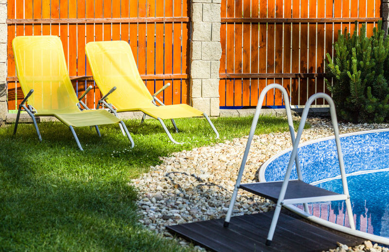 Empty chairs by swimming pool at yard