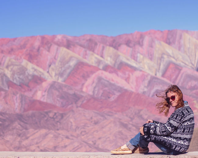 Woman sitting on colored mountain